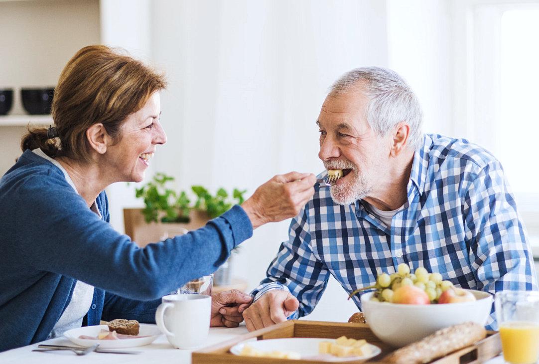 caregiver assisting senior man on eating