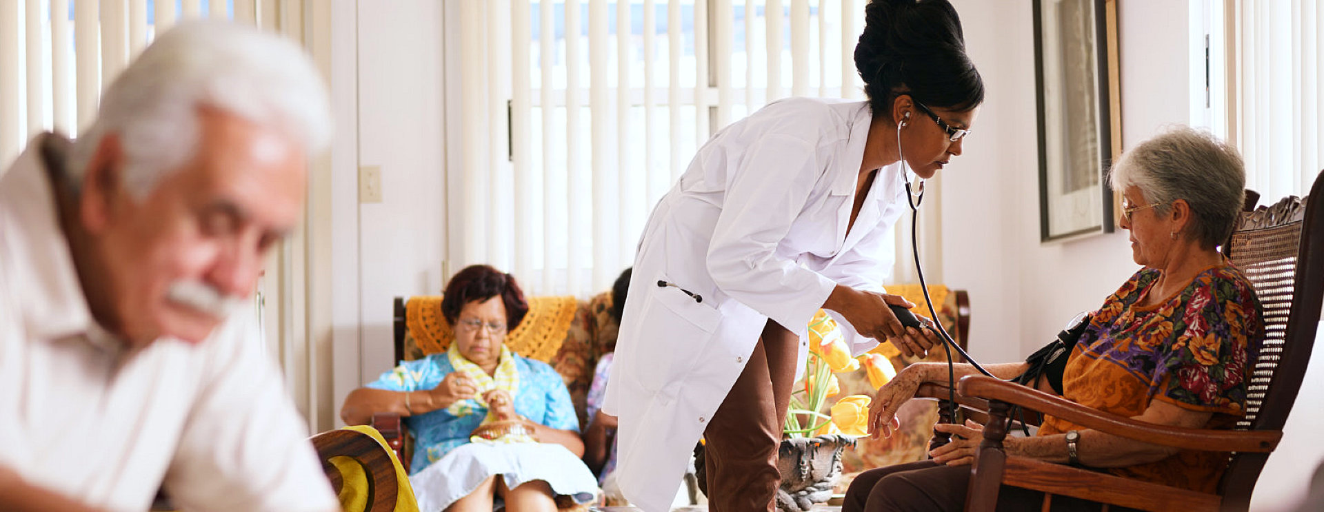 nurse checking on senior woman