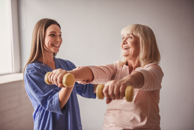 caregiver and her old woman patient doing exercises with dumbbells and smiling