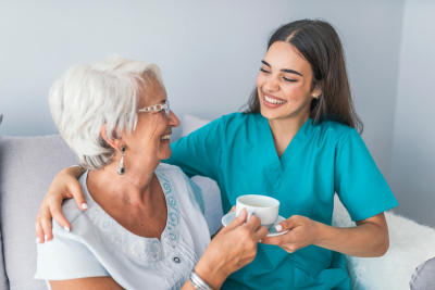 caregiver and her old woman patient smiling at each other